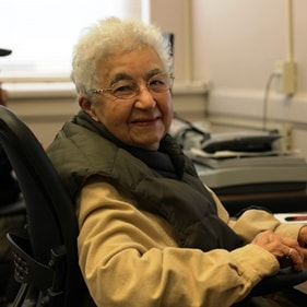 Photo of older woman smiling, in Senior Center computer lab