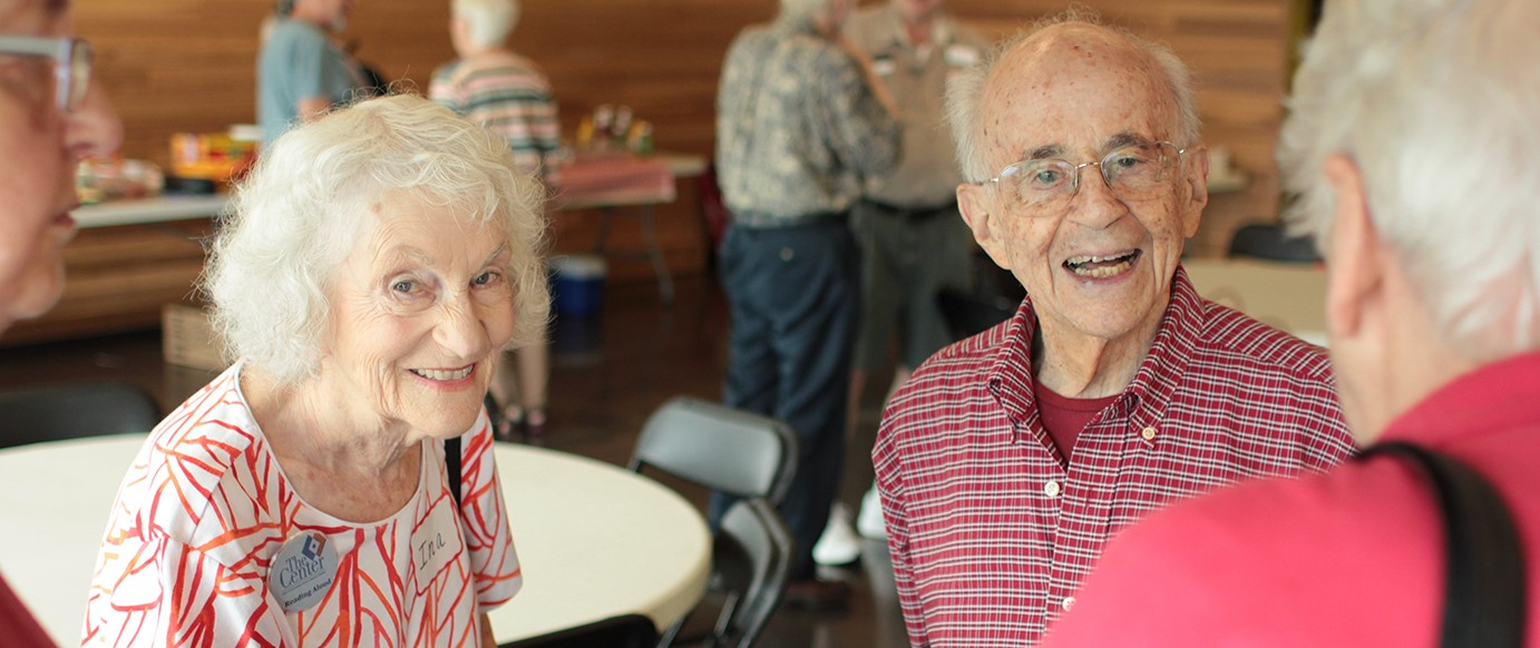 Photo of Senior Center members smiling and talking in a group