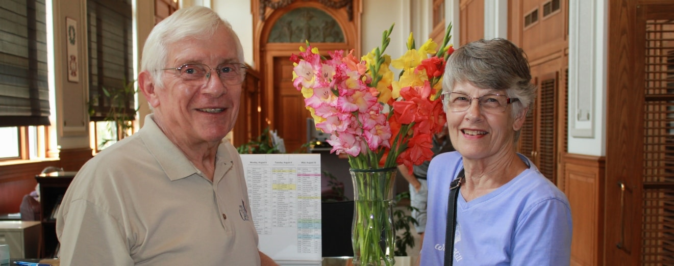 Photo of two older adults greeting visitors in Senior Center's historic lobby