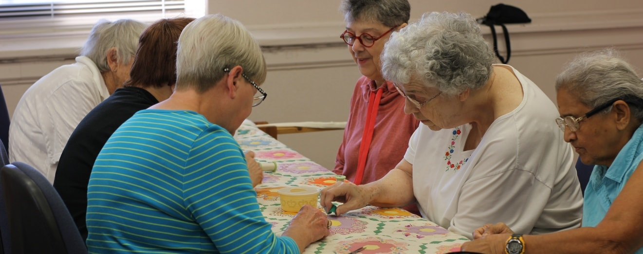 Photo of Senior Center volunteers hand quilting a quilt on a frame