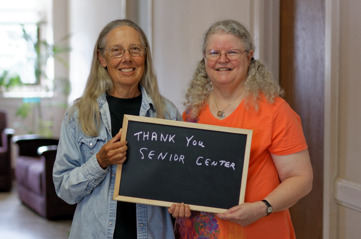 Photo of two Senior Center members holding a sign that says thank you
